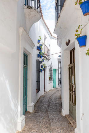 Narrow street of the White Villages of Andalusia, with flower pots hanging from the walls, Spain