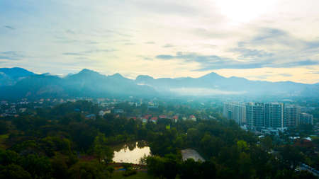 Aerial photography of a mist covered mountain in Ipoh from a public recreational park during sunrise. Standard-Bild
