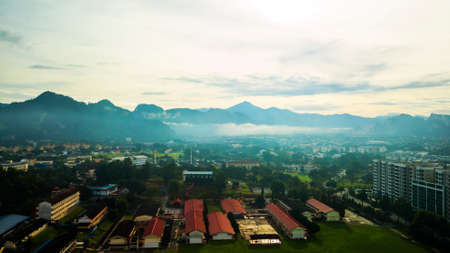 Aerial photography of a mist covered mountain in Ipoh during sunrise with a school in the foreground.