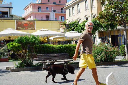 A smiling relaxed senior in yellow shorts and khaky polo turning head towards camera, walking his dog in the centre of Tropea, Calabria, Italy in August, 2019.