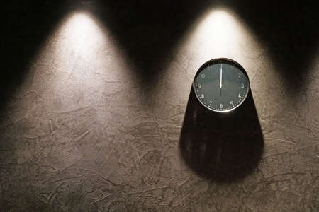 Black simple analog clock showing midnight hanging on the dark brown wall with copy space on the left. Three triangle shadows from above and one rounded shadow under the clock.