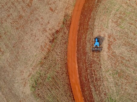 Aerial view of a tractor harrowing the soil to plant soybeans in Brazil