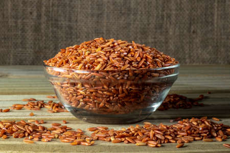 red rice on glass bowl isolated on wooden table in Brazil