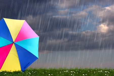 monsoon clouds: rainbow colored umbrella s in heavy rain to use as background