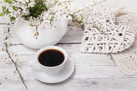 Spring blossom cherry flowers with coffee over wooden background  photo