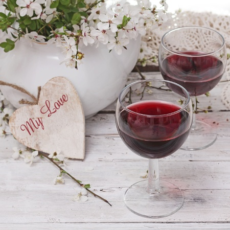 re wine and spring blossom cherry flowers over wooden background  photo