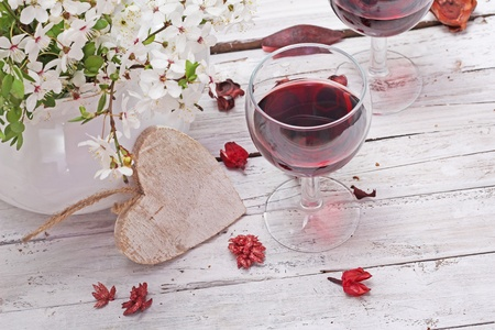 red wine and spring blossom cherry flowers over wooden background