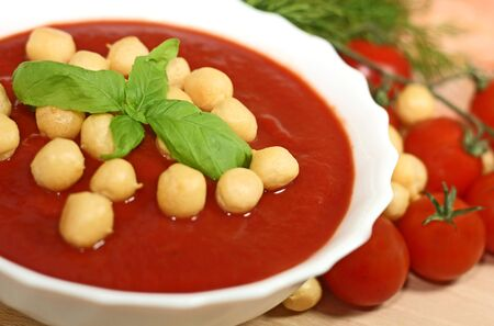 Closeup of bowl of tomato soup garnished with basil leaves  photo