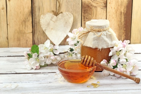 Honey in a glass jar and flower sunflower on a wooden table   photo