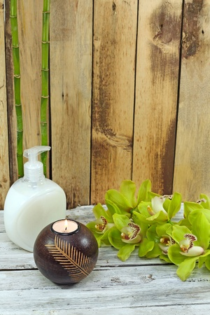 spa frame from bamboo grove, green orchid and candle on the old wooden backgrou photo