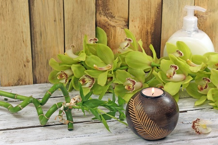 spa frame from bamboo grove, green orchid and candle on the old wooden backgrou