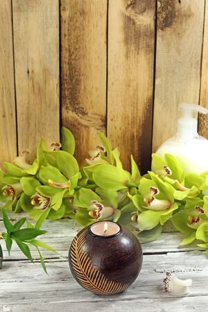 massage symbol: spa frame from bamboo grove, green orchid andcandle on the old wooden backgrou