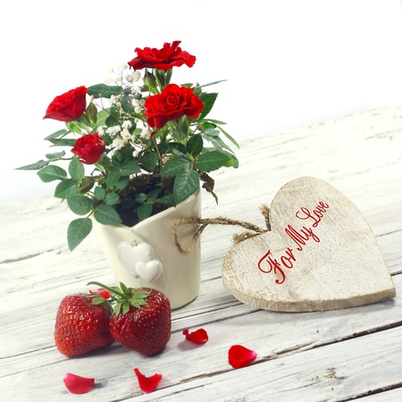 red roses, heart and strawberry on wooden table photo