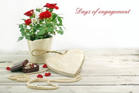 red roses, heart and jewelry on wooden table photo