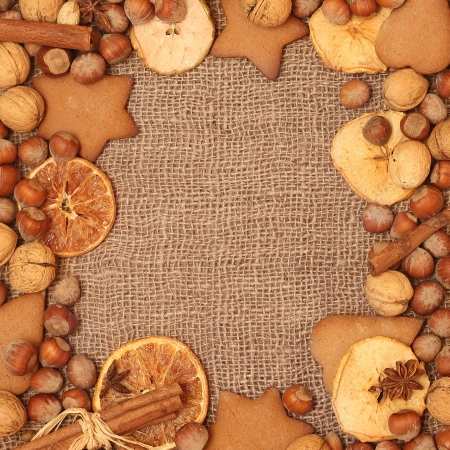 Christmas frame  Christmas spices and dried orange sliceson on canvas background  photo