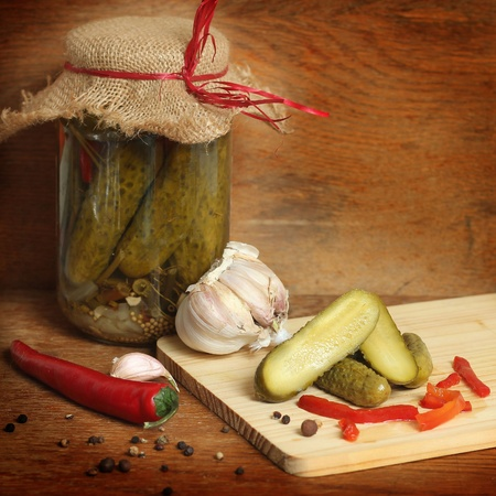 spiced: Glass jar with the cucumbers on a wooden table  Stock Photo