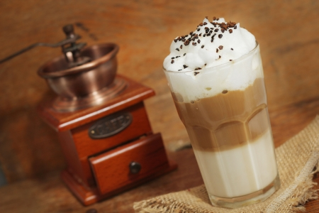 latte macchiato: latte macchiato with cocoa powder and coffee beans on wooden table Stock Photo