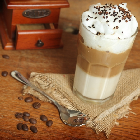 brewed: latte macchiato with cocoa powder and coffee beans on wooden table