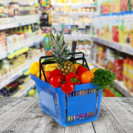 Shopping basket with groceries  on shop of background photo