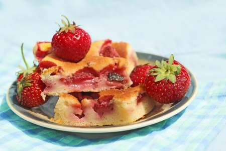 A piece of cake with strawberries on plate on blue background Stock Photo - 20700001