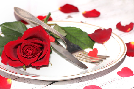 dinning table: Romantic table setting  with roses plates and cutlery Stock Photo