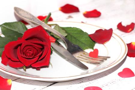 Romantique table avec des roses assiettes et couverts