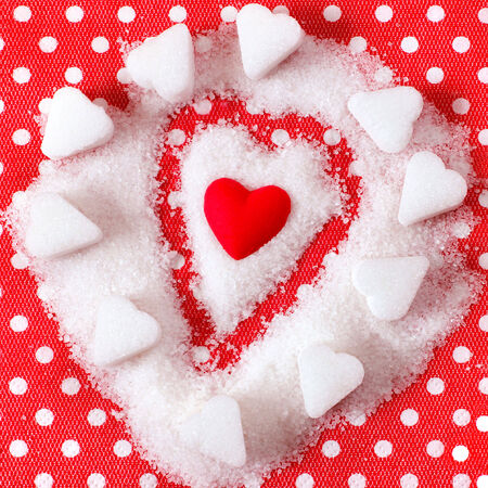 Heart in sugar on red background. Valentines symbol  photo