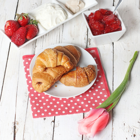 coffe: breakfast with croissants, strawberry  and cup of coffe on white wooden table