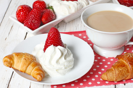 breakfast with croissants, strawberry  and cup of coffe on white wooden table photo