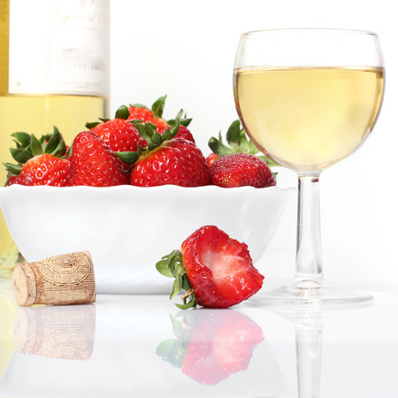 whie: whie  wine bottle and glass and fresh strawberries isolated on white