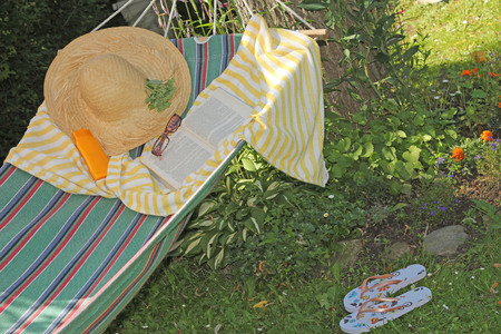 rest day: Hammock, book, hat, and glasses on a sunny summer day Stock Photo