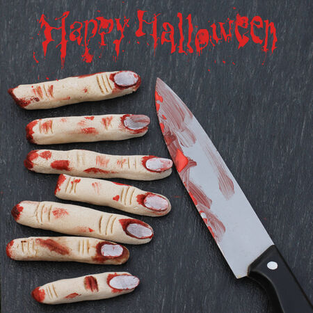 Halloween concept : fingers in blood with knife on a dark background photo