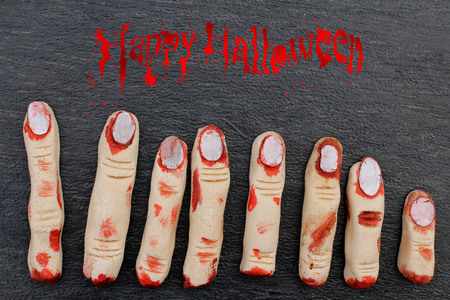 Halloween concept : fingers in blood on a dark background photo
