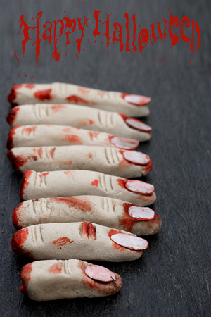 Halloween concept : fingers in blood with on a dark background photo
