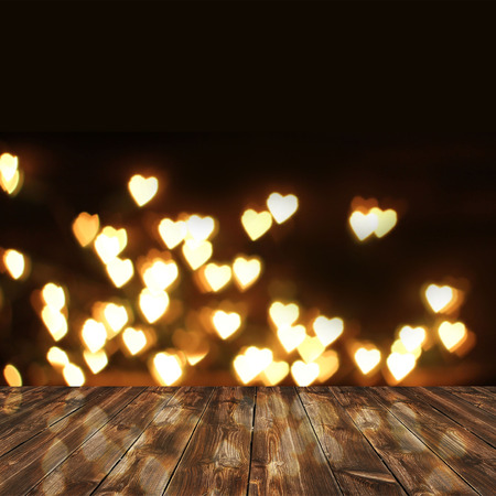 wooden deck table over heart bokeh background. Valentines day background