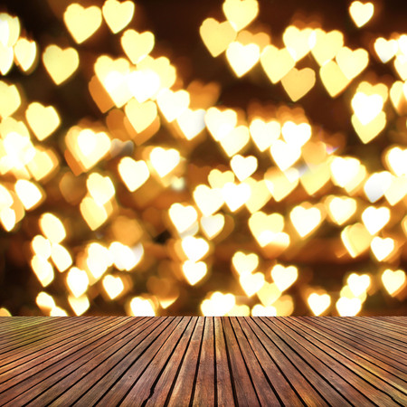 holiday lights display: wooden deck table over heart bokeh background. Valentines day background