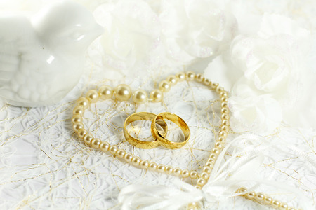 marital: Two golden wedding rings with seamless flower decorations Stock Photo