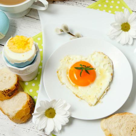 desayuno romantico: Pascua ajuste de la tabla con flores y huevos en tabla de madera Foto de archivo