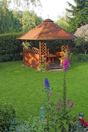 tuinhuis: Houten zomerhuis in de tuin Stockfoto