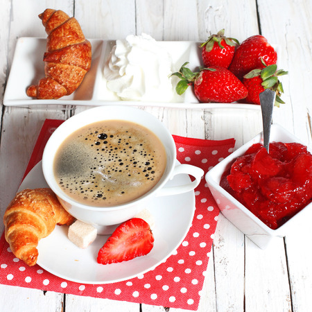 coffe: breakfast with croissants, strawberry  and cup of coffee on white wooden table