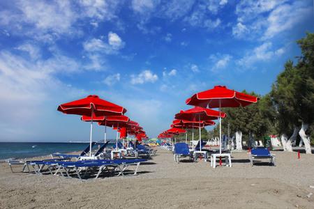 rhodes: red umbrellas on the beach. Greece, Rhodes Stock Photo