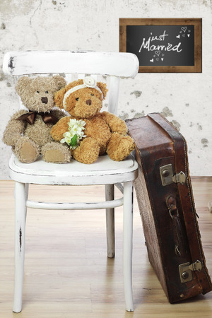 Two in love teddy bears sit on a chair. Wedding  concept 免版税图像