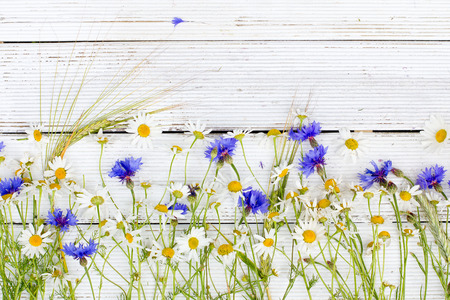yellow wildflowers: Summer wildflowers and rye on wooden background
