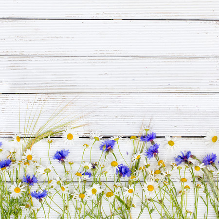 Summer wildflowers and rye on wooden background