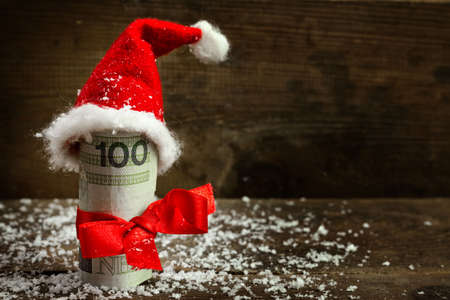 european money: Gift money with red ribbon and Santa cap