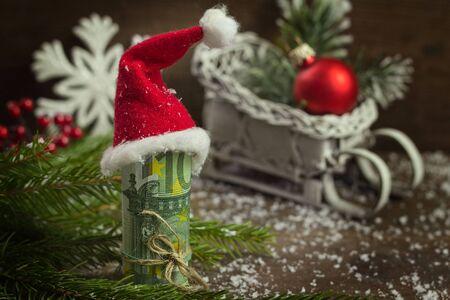 dinero euros: dinero de regalo con cinta roja y el casquillo de Santa Foto de archivo