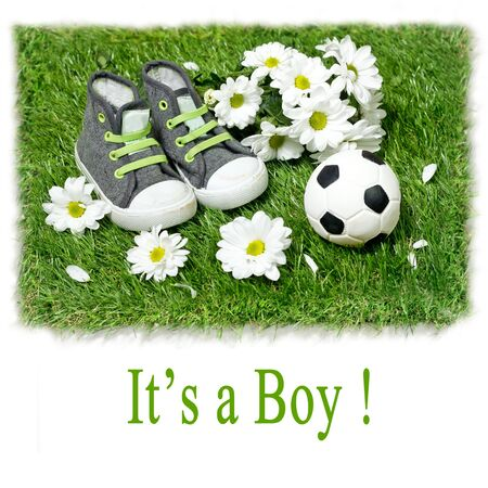 baby boys: Boys shoes and a football ball on on the grass. Concept for baby shower Stock Photo