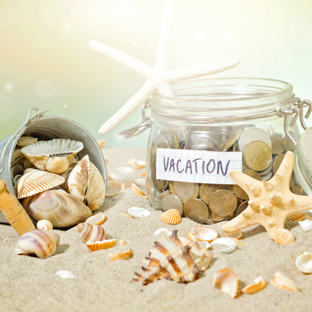 Savings for vacation. Coins and shell at the beach