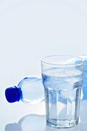 vaso con agua: El agua en botellas y vidrio