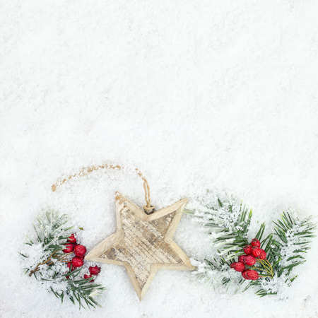 whitespace: background of spruce twig, rowan and  star in the snow Stock Photo